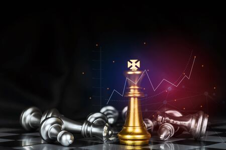golden king surrounded with silver chess pieces on chess board game competition with graphic graph chart on dark background, chess battle, victory, success, team leader, business strategy concept 版權商用圖片