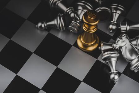 top view shot of golden king surrounded with silver chess pieces on chess board game competition with dark background, chess battle, victory, success, team leader, teamwork, business strategy concept 版權商用圖片
