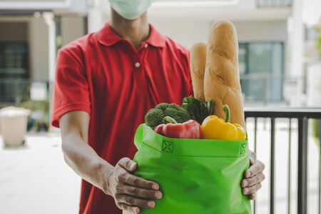 food delivery service man with protection face mask in red uniform holding fresh food set bag waiting for customer at door home, healthy food, express delivery, food delivery, online shopping concept 版權商用圖片