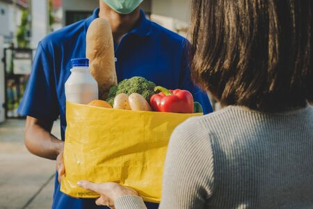woman customer receiving fresh food set bag from food delivery service man with protection face mask in blue uniform at door home, express delivery, quarantine, virus outbreak, food delivery concept