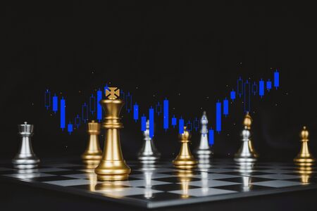 gold king surrounded with silver chess pieces on chess board game competition with graphic graph chart on dark background, chess battle, victory, success, team leader and business strategy concept 版權商用圖片