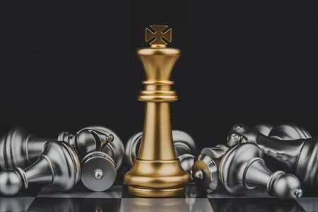Winner. shot of golden king surrounded with silver chess pieces on chess board game competition with dark background, chess battle, victory, success, team leader, teamwork, business strategy concept 版權商用圖片