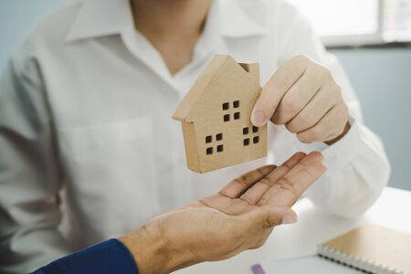real estate broker manager giving house model to customer after signing contract for buying house in estate agent office, digital marketing, finance, home loan contract, buy and sell house concept