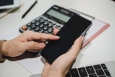 young woman using digital mobile phone working and calculate about finance information on desk at home office, financial business strategy, shopping online, digital marketing and technology concept 版權商用圖片 - 146068903