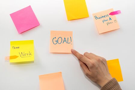 Goal. business woman hand pointing with colored sheets sticky note paper on white board background in office, business meeting, brainstorming, creative, digital online marketing, financial concept
