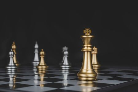 Leader. gold king with silver chess pieces on chess board game competition on dark background, business plan, chess battle, victory, success, team leader, teamwork and business strategy concept 版權商用圖片