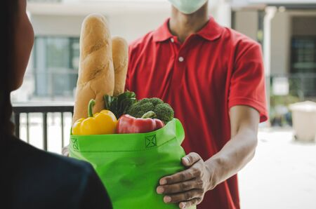 woman customer receiving fresh food set bag from food delivery service man with protection face mask in red uniform at door home, express delivery, quarantine, virus outbreak, food delivery concept