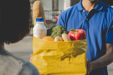 food delivery service man with protection face mask in blue uniform holding fresh food set bag to customer at door home, express delivery, quarantine, virus outbreak, takeaway food delivery concept