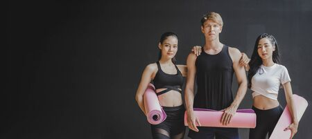 copy space banner. group of young sporty multicultural people slim body holding yoga mat at dark black wall background in fitness gym studio resting after yoga class, sport and yoga training concept
