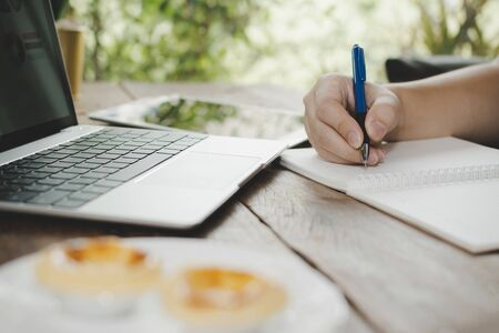 man relaxed writing and working with digital laptop computer with egg tart 