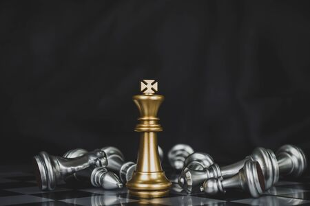 Winner. gold king surrounded with silver chess pieces on chess board game competition with copy space on dark background, chess battle, success, team leader, teamwork and business strategy concept 版權商用圖片