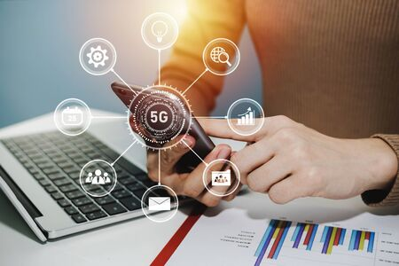 5G. woman hand using digital mobile phone with virtual graphic icon, laptop computer and report on desk at home office, digital marketing, work from home, business finance, network technology concept