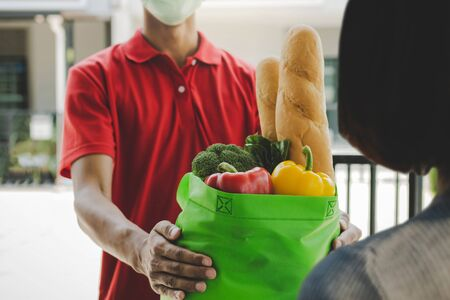 food delivery service man with protection face mask in red uniform holding fresh food set bag to customer at door home, express delivery, quarantine, virus outbreak, takeaway food delivery concept 版權商用圖片