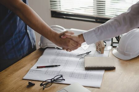 engineer, interior designer and architect hands shaking greeting start up plan new project contract with blueprint on desk in meeting room office at construction site, partnership, contractor concept