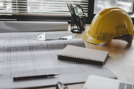 construction working tool, blueprint and yellow safety helmet on architect workplace desk in meeting room office center at construction site, construction, engineering tools and architectural concept 版權商用圖片