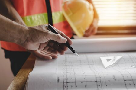 professional architect, engineer or interior designer hands drawing with pen and blueprint on workplace desk in office center at construction site, construction, engineering and architectural concept