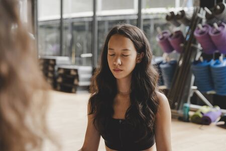 pretty young woman slim body doing yoga in Padmasana or Lotus yoga pose on yoga mat with instructor in class at fitness gym, relax, healthy lifestyle, fitness, workout and sport training concept
