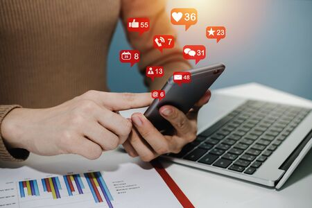 hand using social network on digital mobile phone with virtual icon, laptop computer and report on desk at home office, digital marketing, work from home, business finance, network technology concept 版權商用圖片