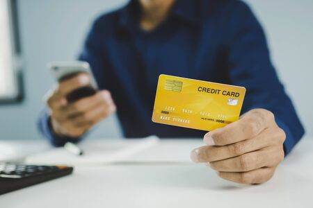 young man hand holding mock up credit card and using digital mobile phone paying family budget cost bill. online shopping, digital marketing, electronic pay, online payment, digital technology concept