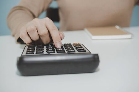 business woman working and calculating about finance with calculator and document report on desk at home, work from home, financial, quarantine, technology, accountant and business financial concept 版權商用圖片