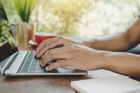 young man hand relaxed and working with digital laptop computer and red coffee cup on desk at cafe, self quarantine, work from home, digital marketing, business finance, network technology concept 版權商用圖片
