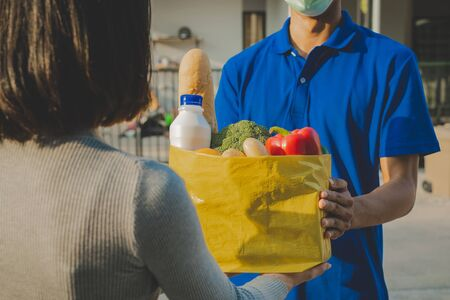 delivery service man with protection face mask in blue uniform holding fresh food set bag for customer at door home, grocery, healthy food, express delivery, food delivery, online shopping concept 版權商用圖片