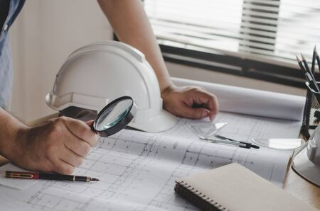 hands engineer or architect working on blueprint and white safety helmet on workplace desk in meeting room project at construction site office, contractor, engineering and construction concept