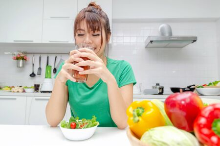 pretty asian woman slim body in green shirt dieting and drinking homemade detox juice with fresh vegetable salad sitting in at house, lifestyle, good healthy, diet food, fruit juice and drink concept 版權商用圖片