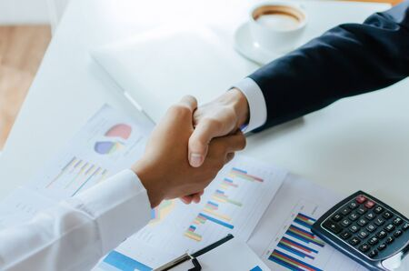 Partnership. two business investor people partner handshake after finishing up business meeting with financial statistics report on desk in office, negotiation, investment and financial concept