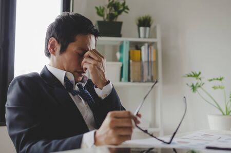 tired asian young businessman feeling stressed and taking off eyeglasses feels eye strain fatigue after long office work on computer, overwork, office syndrome, business problem and financial concept