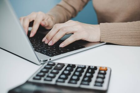 businesswoman hand typing and working on digital laptop computer, calculator on desk at home office, digital marketing, accountant, search engine, work from home, business finance, technology concept 版權商用圖片