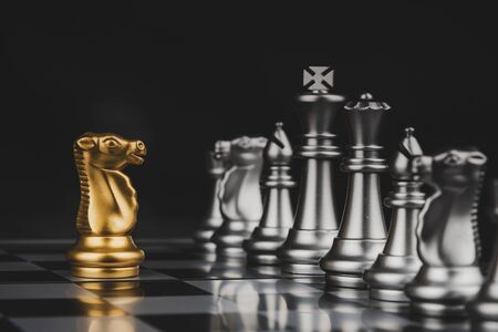 Leadership. gold horse chess with silver chess pawns pieces on chess board game competition on dark background, chess battle, success, management, team leader, teamwork and business strategy concept 版權商用圖片