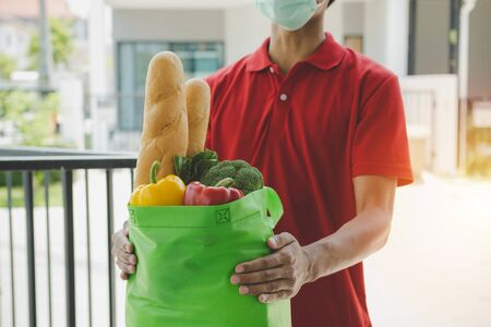handsome delivery man with protection face mask in red uniform holding fresh food set bag waiting for customer at door home, healthy food, express delivery, food delivery, online shopping concept