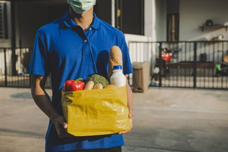 handsome delivery man with protection face mask in blue uniform holding fresh food set bag waiting for customer at door home, healthy food, express delivery, food delivery, online shopping concept
