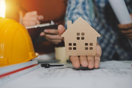 hand of engineer and architect showing house model and working on blueprint on desk in meeting room project at construction site office, home loan contractor, engineering and construction concept