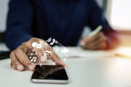 man in blue shirt hand using on digital mobile phone with virtual digital icon and writing on document report on desk at home office, work from home, digital marketing and financial business concept