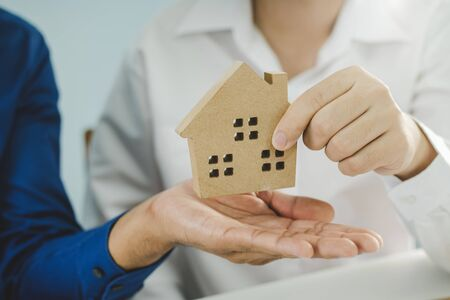 hand of real estate broker manager giving house model to customer after signing contract for buying house in estate agent office, real estate, finance, home loan contract, buy and sell house concept