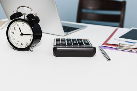retro style black alarm clock with digital laptop computer, calculator, digital mobile tablet and document report on white desk at home office, night working late, business finance, object concept