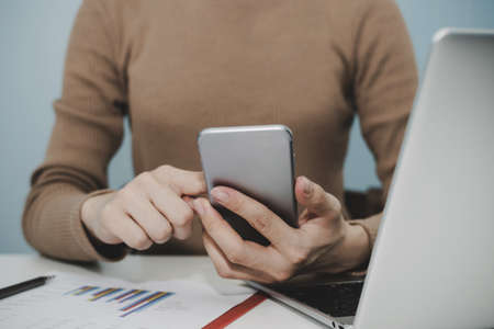 businesswoman hand working with digital mobile smartphone, laptop computer and report on desk at home office, digital marketing, work from home, business finance, internet network technology concept 版權商用圖片
