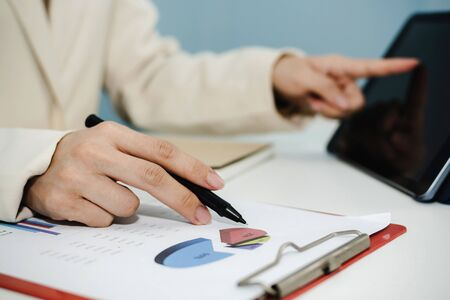 attractive businesswoman in white suit working and calculating about finance with, document report and digital mobile tablet on desk at office, digital online marketing and financial business concept