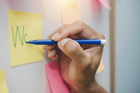 Work. businessman hand writing with colored sheets sticky note paper on white board background in home office, business meeting, brainstorming, creative, digital online marketing, financial concept 版權商用圖片