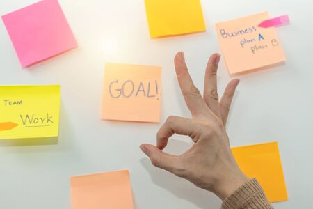 Goal. business woman showing OK hand with colored sheets sticky note paper on white board background in office, business meeting, brainstorming, creative, digital online marketing, financial concept