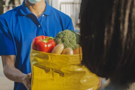 food delivery service man in blue uniform wearing protection face mask holding fresh food set bag to customer at door home, express delivery, quarantine, virus outbreak, takeaway food delivery concept 版權商用圖片