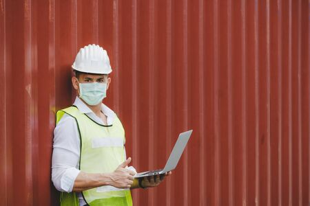 caucasian engineer control worker wearing protection face mask working on digital laptop computer with cargo container in background at cargo harbor, industrial, logistic import and export concept