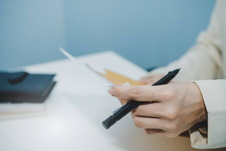 attractive businesswoman in white suit hand open business report from document envelope and working on desk in meeting room at home office, digital online marketing and financial business concept