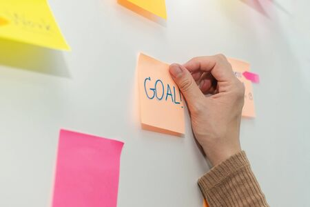 Goal. business woman hand with colored sheets sticky note paper on white board background in office, business meeting, brainstorming, creative, digital online marketing, business financial concept