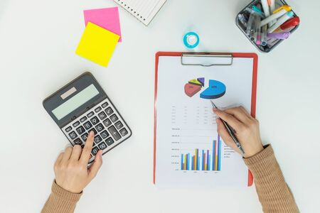 top view of businesswoman working about finance on calculator and document report on white desk at home office, work from home, digital marketing, technology, accountant, business financial concept 版權商用圖片