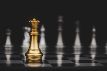 Leadership. gold queen with silver chess pieces on chess board game competition on dark background, chess battle, victory, success, management, team leader, teamwork and business strategy concept