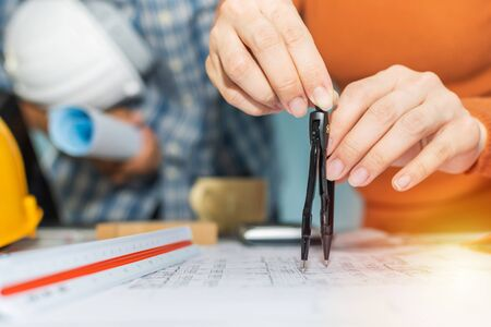 professional architect and interior designer hands drawing with divider compass on blueprint on desk in meeting room office at construction site, construction industrial, engineering business concept