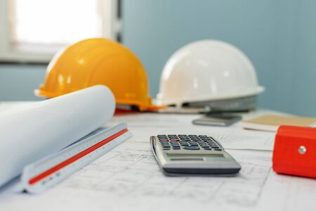construction working tool, calculator, blueprint and safety helmet on architect workplace desk in meeting room office center at construction site, construction, engineering tool, architectural concept